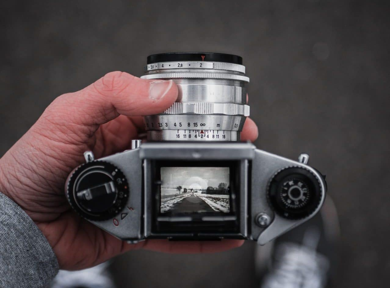 Image of someone taking a picture with an old camera with a top-down viewfinder
